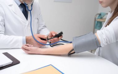 Doctor checking blood pressure of patient