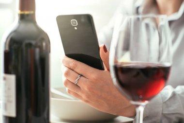Woman using wine app at restaurant