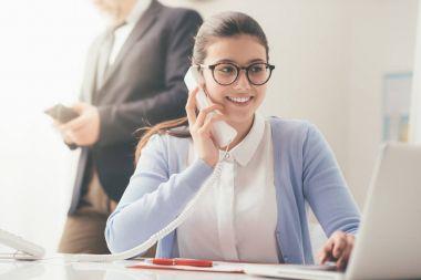 smiling secretary answering phone calls