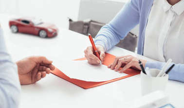 Woman signing car insurance policy