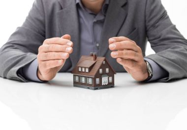 Businessman protecting model house