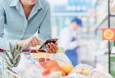 Donna che fa alimentari spesa al supermercato, lei è appoggiata sul carrello e collegamento con il suo concetto di telefono cellulare, applicazioni e vendita al dettaglio