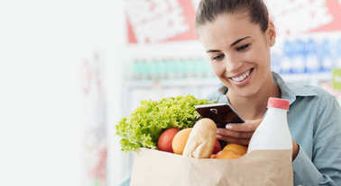 Smiling young woman shopping at the supermarket, she is holding a shopping bag and using her smartphone