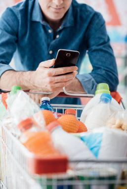 Man shopping at the supermarket, he is leaning in the shopping cart and connecting with his mobile phone