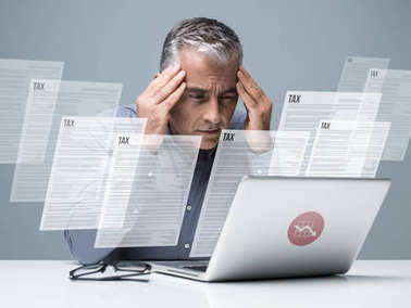 Pensive businessman checking tax forms online using a laptop: finance, taxation and costs concept