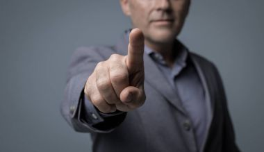 Businessman using a virtual interface and pointing at screen with his index finger