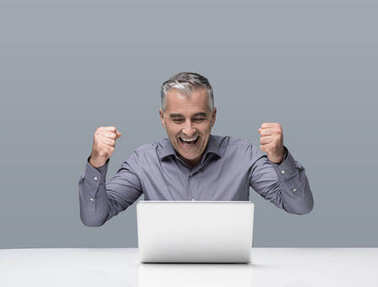 Cheerful mature businessman working at office desk with a laptpop, he is cheering with raised fists, achievement and success concept