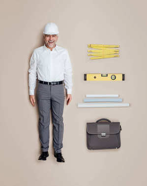 Lifelike engineer and architect male doll with work equipment, he is wearing a safety helmet and smiling, flat lay