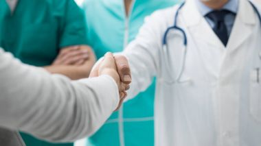 Doctors and patient shaking hands after a consultation at the hospital and medical team, medical exams and healthcare concept