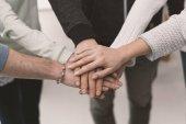 Mladí lidé překrývání ruce dohromady: koncepce týmové práce, spolupráce a podpora