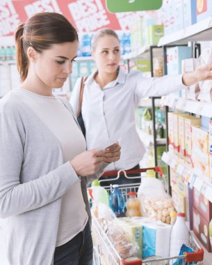 Woman shopping at the supermarket, she is checking a grocery list and searching products on the store shelf