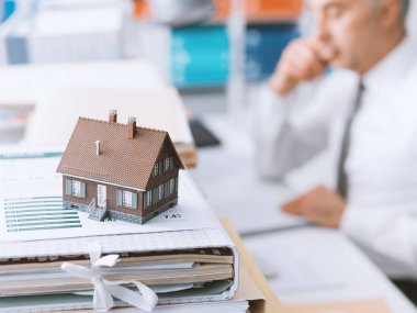 Real estate agent working in the office and piles of paperwork, model house on the foreground and mortgage loan documentation