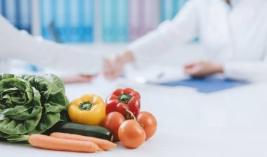 Professional nutritionist working in the office and healthy fresh vegetables on the foreground: diet and health concept