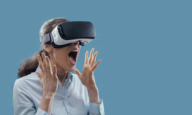 Woman wearing a VR headset and experiencing virtual reality, she is amazed and surprised