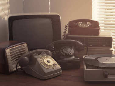 Vintage retro revival objects and second-hand appliances collection on a table: record player, television, radio and rotary dial telephones