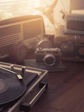 Vintage retro revival objects and appliances assortment on a table, turntable record player on the foreground