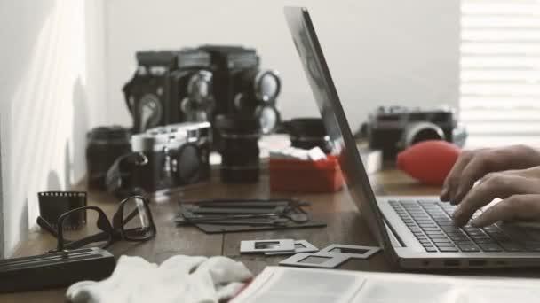 Profesionální fotograf pracující ve svém ateliéru a připojení online pomocí notebooku, ročník filmové kamery a twin objektiv kamery na pozadí
