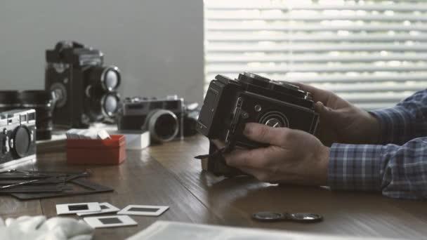 Profi fotós műtermében, dolgozik ő takarítás egy vintage reflexes gép por blower-, hobbi- és fotózás koncepció