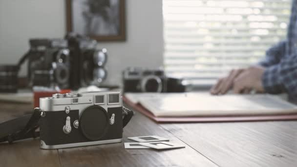 Profesionální fotograf pracuje ve svém ateliéru, sleduje filmové negativy v pořadači, vinobraní fotoaparát a snímky na popředí