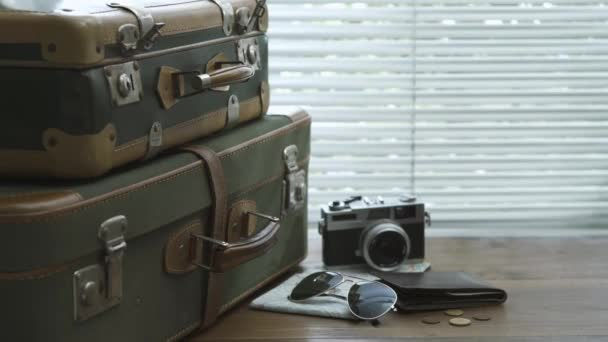 Ready packed vintage suitcases, camera, map and wallet on a desktop: travel and tourism concept