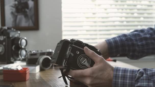 Professioneller Fotograf arbeitet in seinem Atelier, er ist die Reinigung einer Vintage Twin-Spiegelreflexkamera mit einem Tuch, Hobby und Fotografie-Konzept