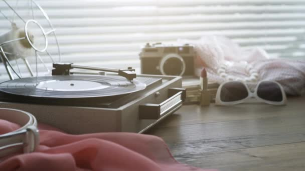 Vintage record player with spinning record and womans accessories on a table, leisure and retro revival concept