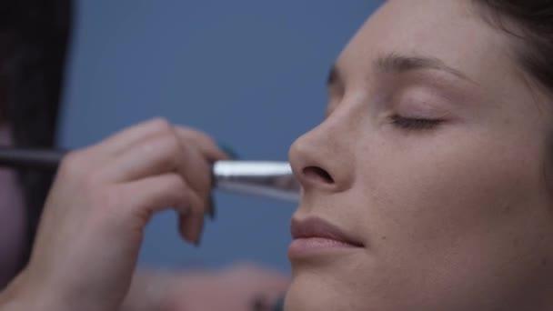 Maskér aplikaci pudru na obličej modelu pomocí make-up štětce, krása a kosmetika koncepce