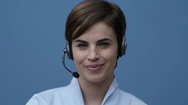 Smiling young call center operator wearing an headset and having a phone call with a customer