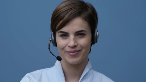 S úsměvem mladá call centrum operátor nošení headsetu pro a mají telefonní hovor se zákazníkem