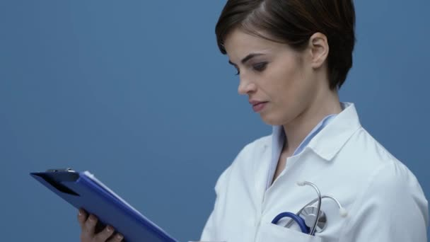 Confident female doctor checking a patients medical records and smiling at camera