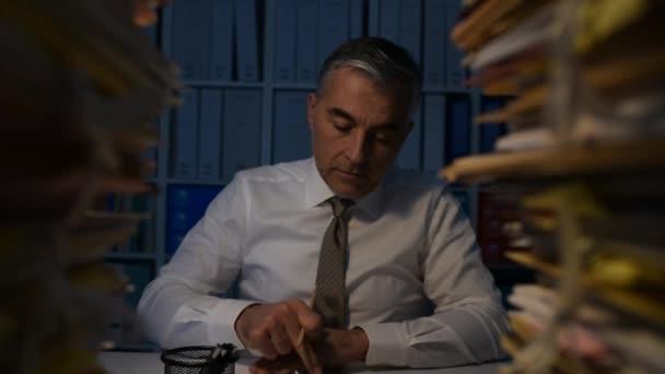 Podnikatel, přetíženi prací, sedí v kanceláři a pracují přesčas pozdě v noci, stůl je plný paprwork, dolly shot
