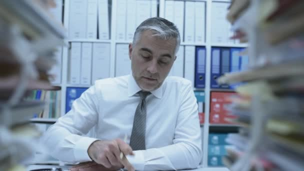 Business executive overwhelmed by work, he has piles of paperwork and files on his desk, dolly shot