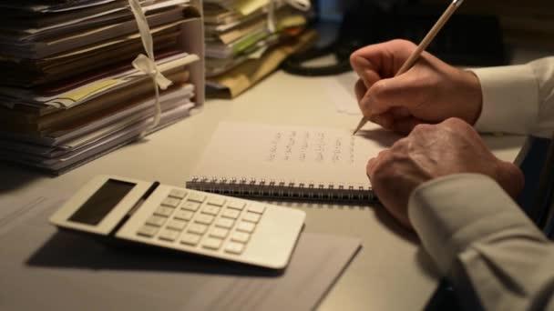 Podnikatel pracuje pozdě v noci v kanceláři a dělá přesčasovou práci, on používá kalkulačka, stůl je plný papírování