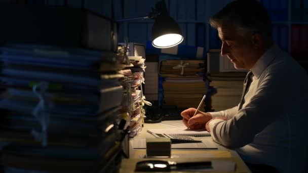 Businessman working late at night in the office and doing overtime work, he is using a calculator, his desk is full of paperwork