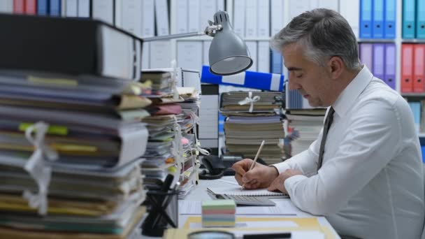 Office worker sitting at office desk and working, he is overloaded with work