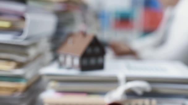 Model domu na hromadu papírování a realitní agent pracující na stůl: realitní, hypoteční úvěry a finanční koncept