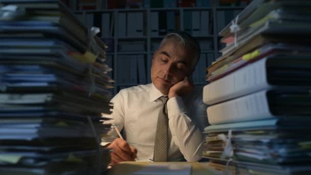 Unavený podnikatel pracuje v noci, je zahlcen prací a jeho stůl je plná papírování, práce přesčas a termíny koncepce