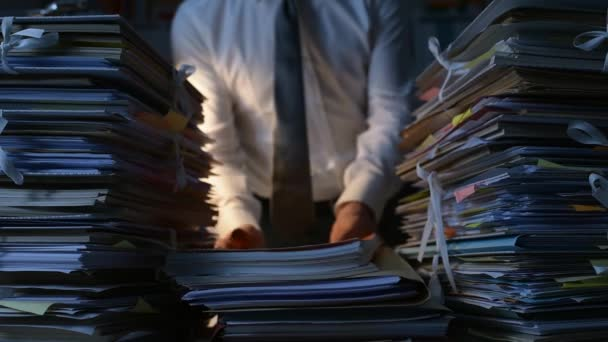 Office clerk stacking paperwork and files on the desk late at night, work overload and bureaucracy concept