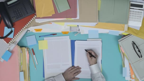 Businessman working at office desk and checking a business document in a folder and writing notes, top view