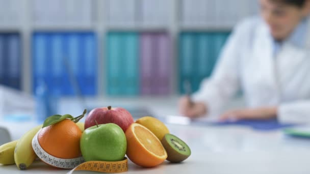 Professional nutritionist working in the office and writing a prescription diet, healthy fresh fruit and tape measure on the foreground