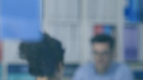 Mladý podnikatel přemýšlet s rukou na bradu a malé obchodní tým pracující na pozadí: obchodní strategie a počáteční koncepce