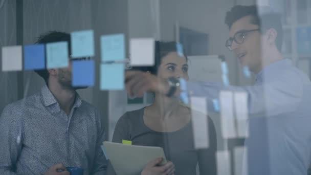 Mladý tým jednání v kanceláři a diskusi o projektu společně směřují na rychlé poznámky na sklenku, nastartovat a koncepce týmové práce