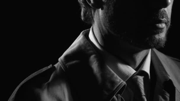 Retro-Noir-Filmfigur: Selbstbewusster Ermittler steht im Dunkeln, dreht sich um und blickt in die Kamera