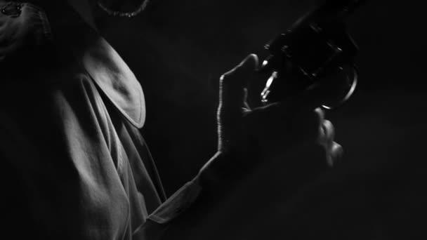 Retro-Detektiv spy hält einen Revolver und zurückziehen des Hammers, er wartet auf der Hut, Noir Film Charakter