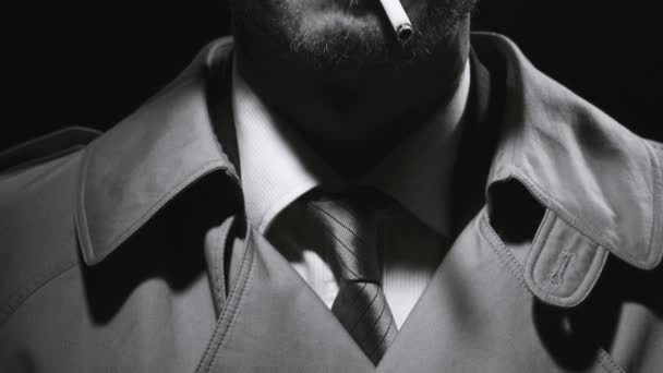 Porträt eines Retro-Noir-Detektiv trägt einen Trenchcoat und einen Filzhut, er raucht eine Zigarette