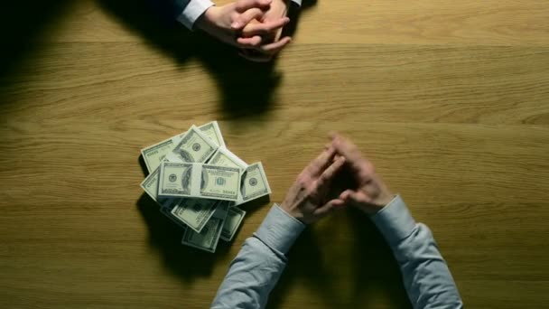 Man in the dark taking money from a dangerous money lender, usury and corruption concept, hands top view