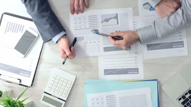 Podnikatelé pracují společně v kanceláři a kontrola finanční zpráva, pohled, nelze rozpoznat lidi ruce shora