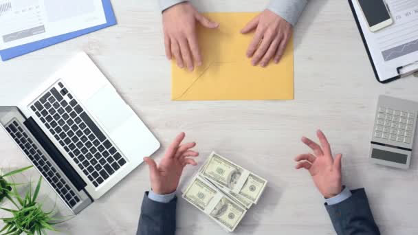 Businessman discussing with a corrupted office worker and giving him bribes in exchange of an envelope, hands top view