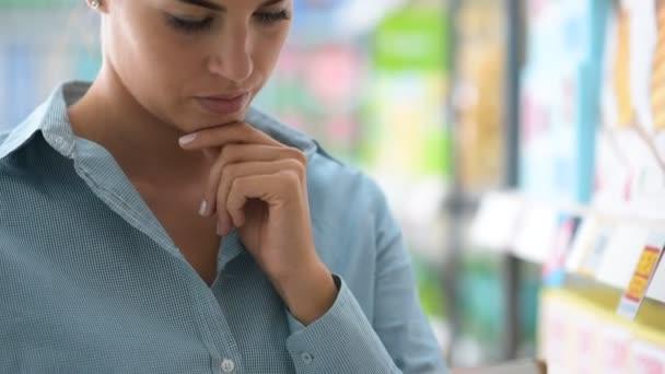 Žena čte štítek produktu