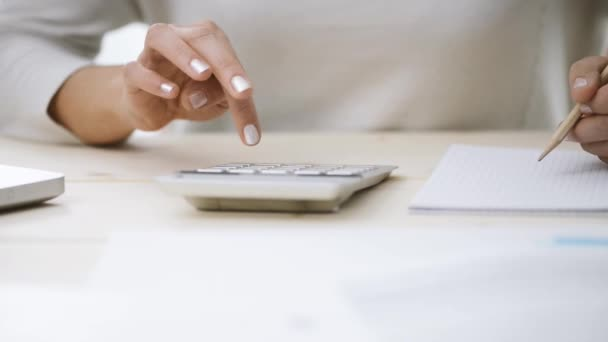 Woman using a calculator and writing notes